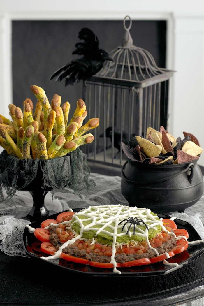 black wooden table decorated with white tulle halloween appetizers black tray with tomatoes meat guacamole dip tortilla chips in black cauldron breadsticks