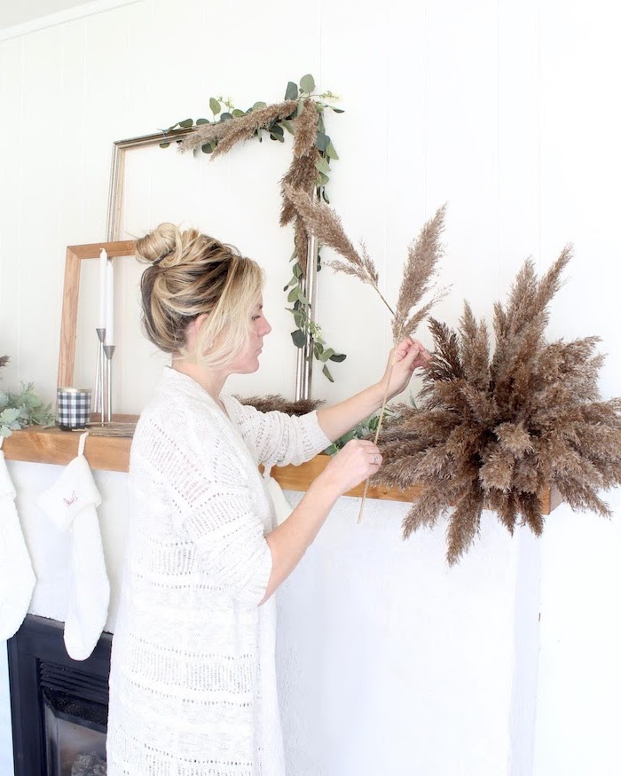 blonde woman decoratingher mantel for christmas wearing white cardigan where to buy pampas grass two candles and stockings