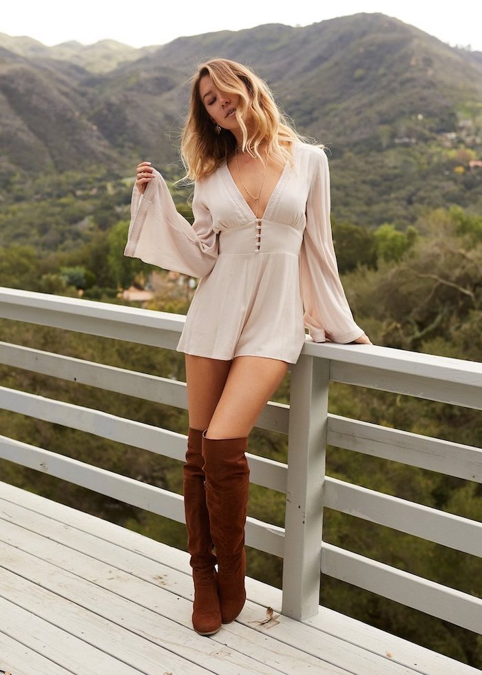 blonde woman standing on a wooden porch fall fashion trends wearing white dress with bell sleeves brown velvet boots