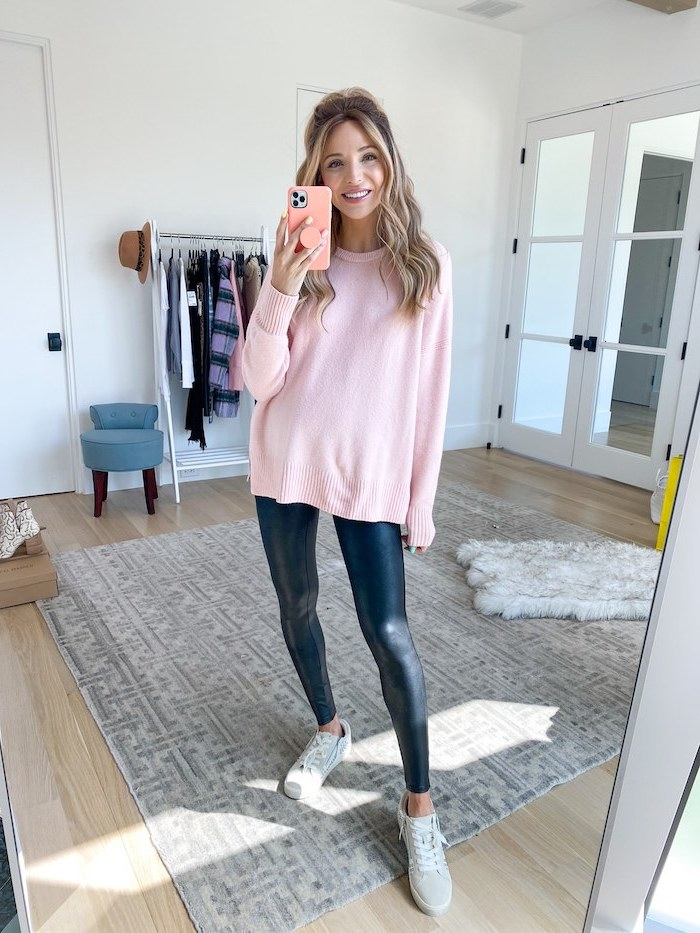blonde woman wearing black leather leggings pink sweater grey sneakers cute outfit ideas for girl taking a mirror selfie