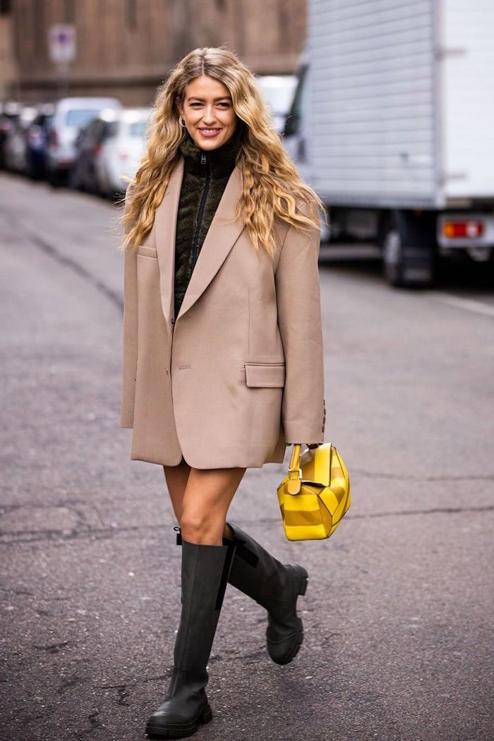 blonde woman wearing over sized grey blazer black boots fall outfits for women carrying small yellow bag