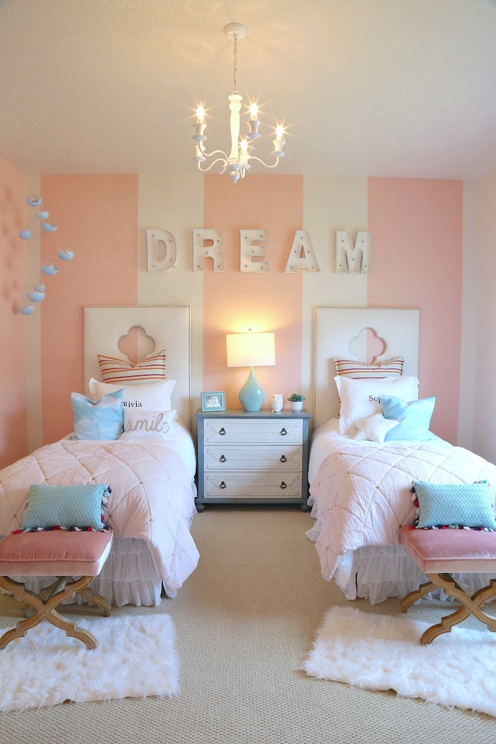 blue throw pillows on two single beds night stand between them cozy teenage girl room pink white striped wall dream written on it