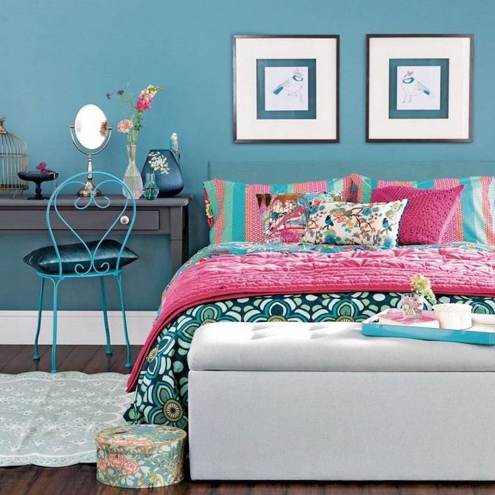 blue wall teenage girl beds double bed with colorful throw pillows and blankets dark wooden floor black desk
