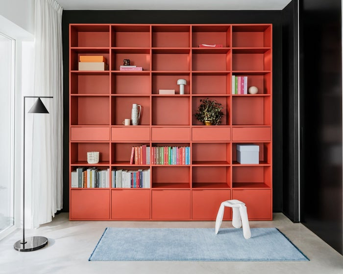 bookcase ideas large red bookcase with drawers and lots of shelves black wall behind it blue carpet on the floor
