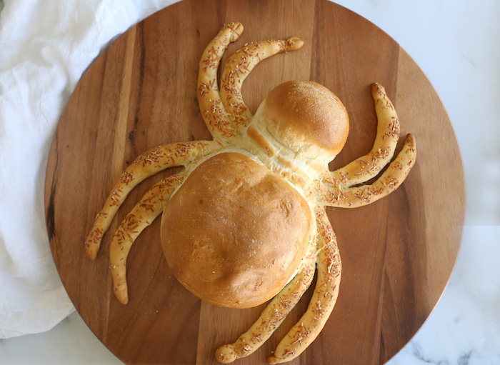 bread baked in the shape of a large spider easy halloween appetizers placed on wooden cutting board placed on white surface