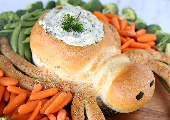 bread baked in the shape of spider with dip inside easy halloween appetizers baby carrots peas broccoli on the side