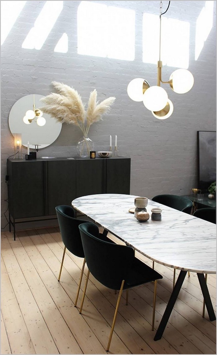 brick accent wall behind black cupboard with a glass vase with dried pampas grass inside marble dining table black chairs