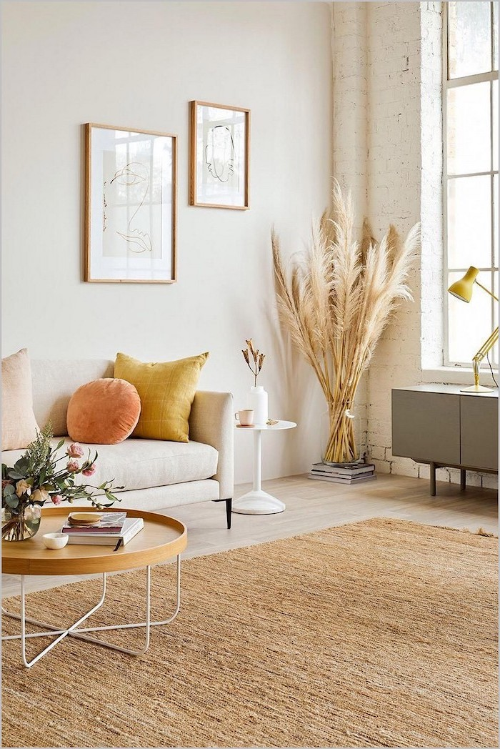 brick accent wall in living room with white sofa wooden table wooden floor with large carpet dried pampas grass inside glass vase in the corner