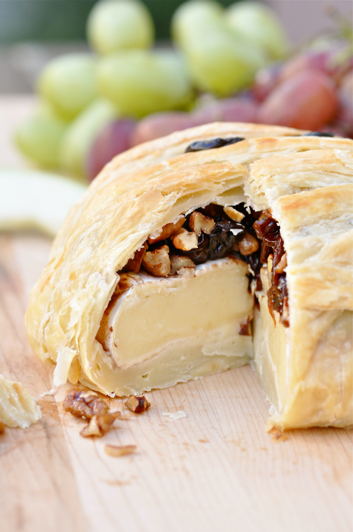 brie cheese baked with jam and walnuts inside dough as mummy halloween finger foods placed on wooden surface