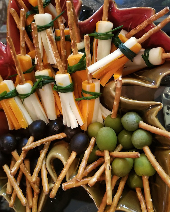 broomsticks made of crackers with cheese olives grapes arranged in ceramic bowl halloween appetizers
