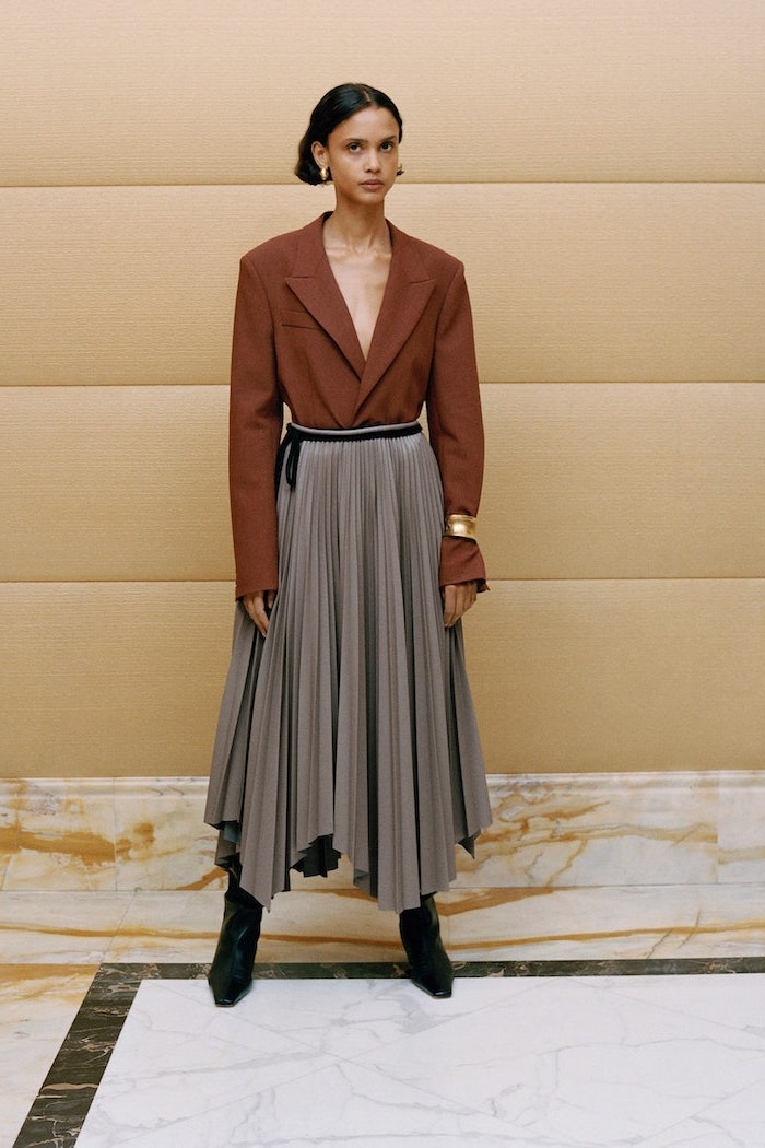 brown blazer tucked into long gray pleated skirt worn with black boots fall fashion trends worn by woman with short black hair