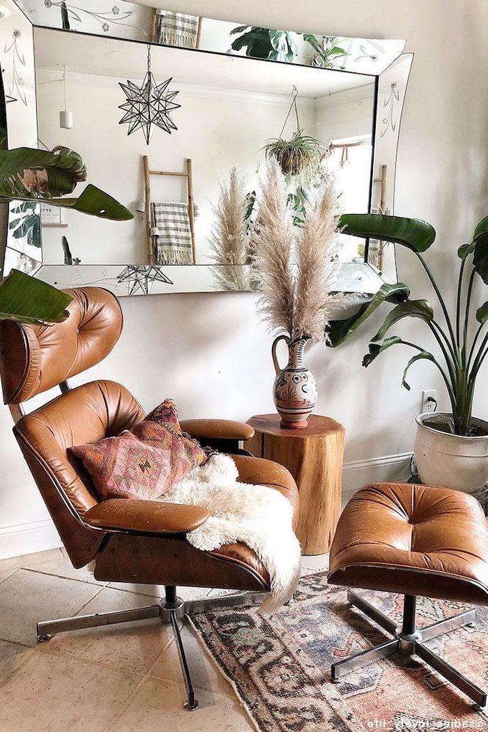 brown leather armchair ottoman small wooden vase next to it artificial pampas grass ceramic jug with pampas grass inside