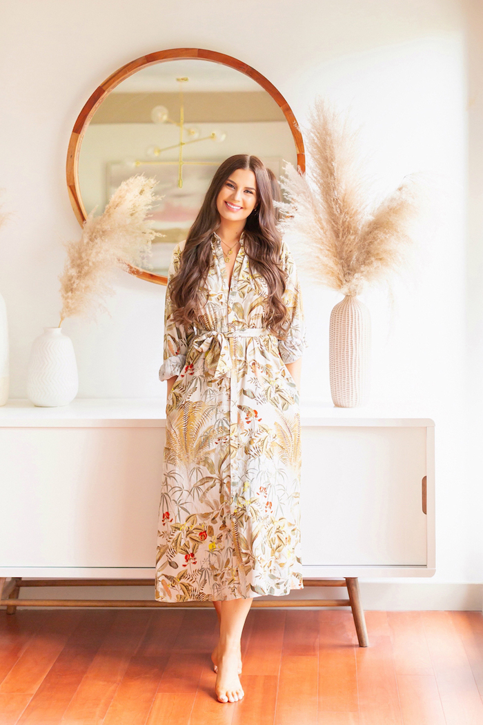 brunette woman wearing colorful dress leaning on white cupboard with two ceramic vases with colored pampas grass round mirror on white wall