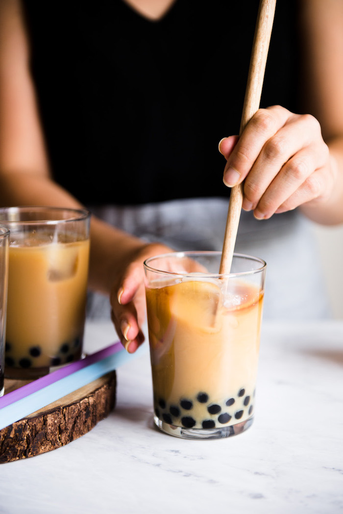 bubble tea step by step milk and boba being stirred with wooden spoon how to make milk tea glass placed on marble surface