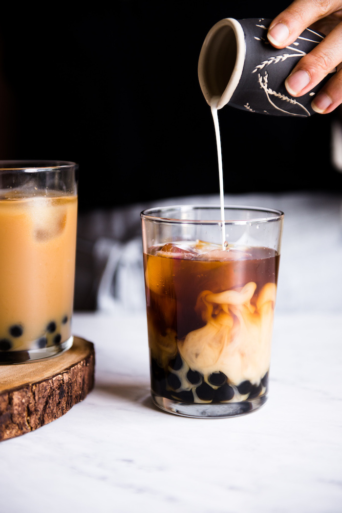 bubble tea step by step milk being poured into glass filled with boba ice and tea how to make milk tea placed on marble surface