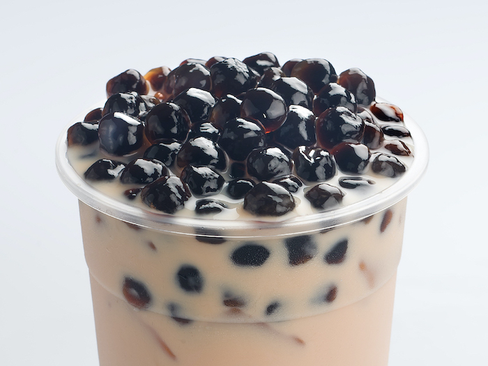 bubble tea with lots of boba tapioca pearls poured into plastic cup how to make boba white background