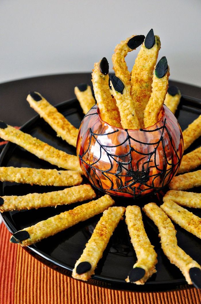 cheddar sticks with breadcrumbs placed on black plate arranged around red bowl halloween themed food black nuts for nails
