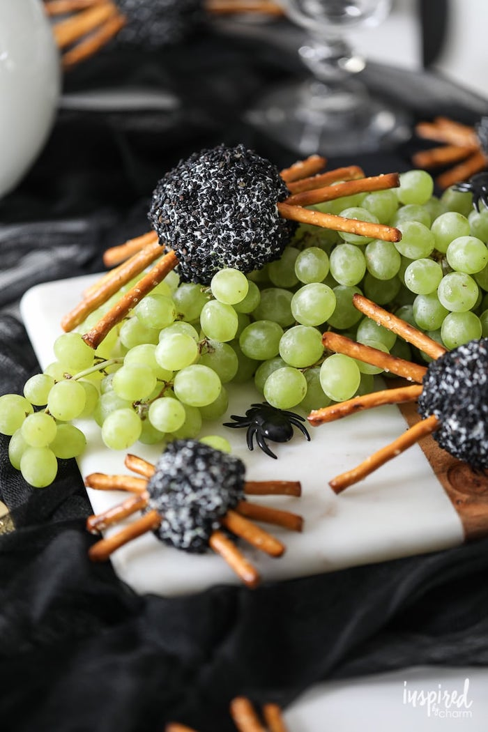 cheeseballs with pretzels as spiders halloween party appetizers placed on wooden cutting board with grape