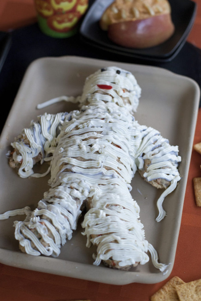 cheesy mummy recipes halloween party snacks placed on gray baking tray orange table cloth crackers on the side