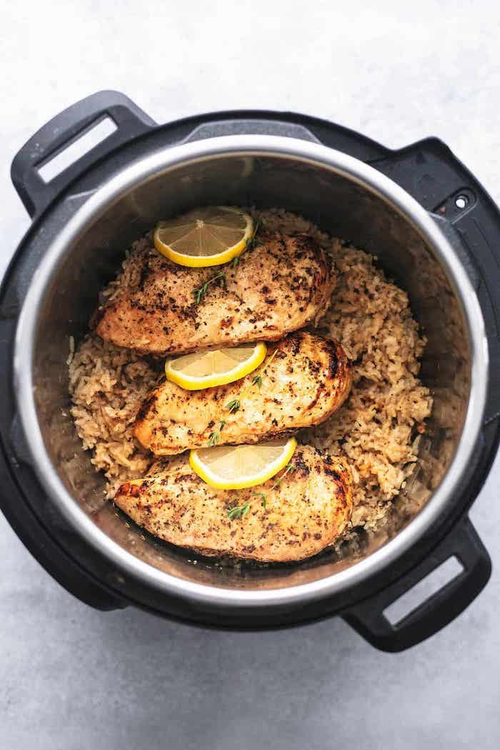 chicken breasts with lemon slices between them best instant pot recipes placed on top of rice cooked in instant pot