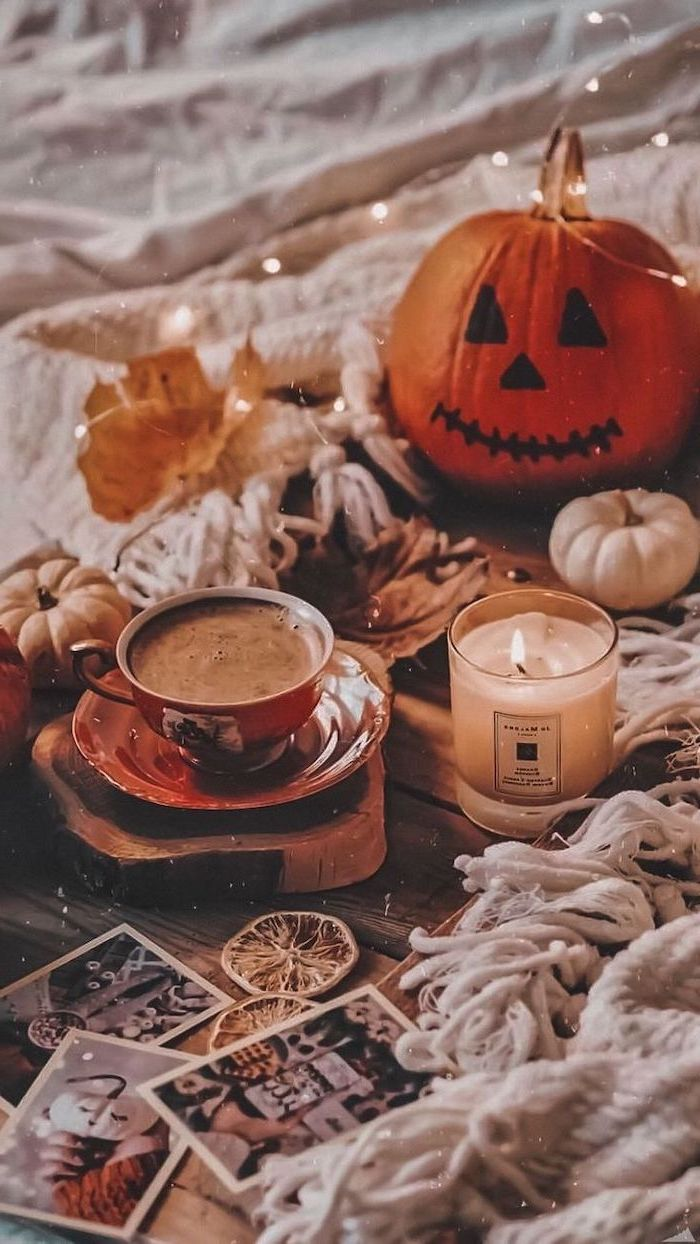 coffee cup next to lit candle carved pumpkin placed on wooden floor with white blankets aesthetic fall wallpaper