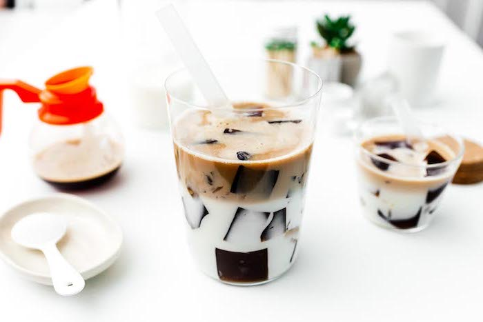 coffee jelly made with ice in two separate layers of milk and coffee how to make milk tea glasses placed on white surface