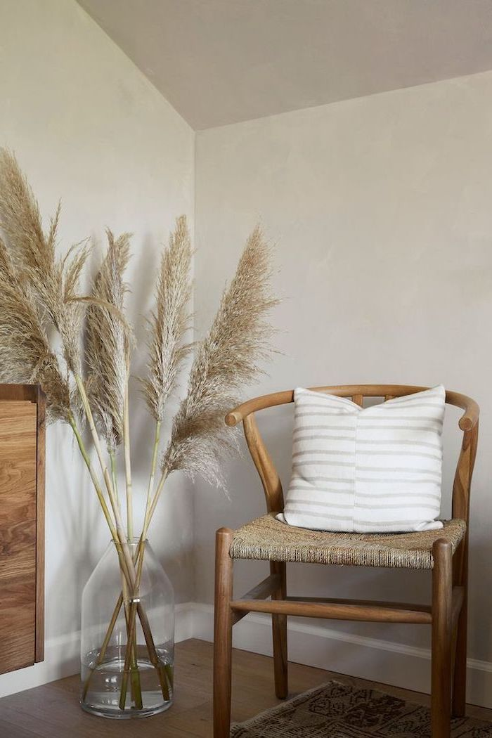 colored pampas grass wooden chair with white pillows glass vas with pampas grass white walls and wooden floor
