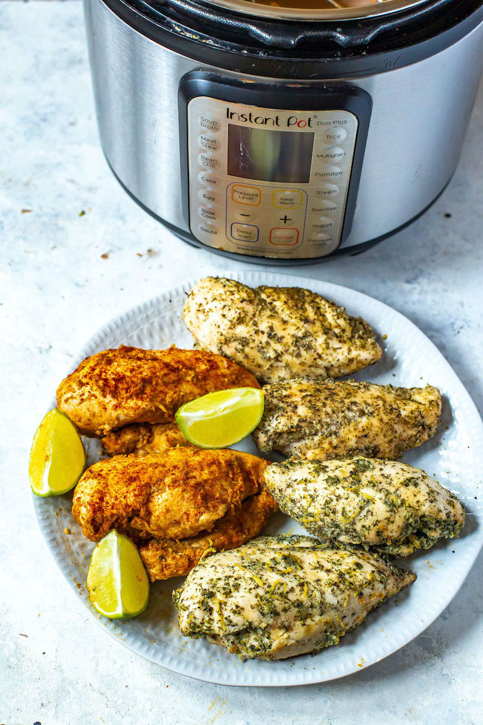 cooked chicken breasts with lime wedges on white plate best instant pot recipes placed in front of instant pot