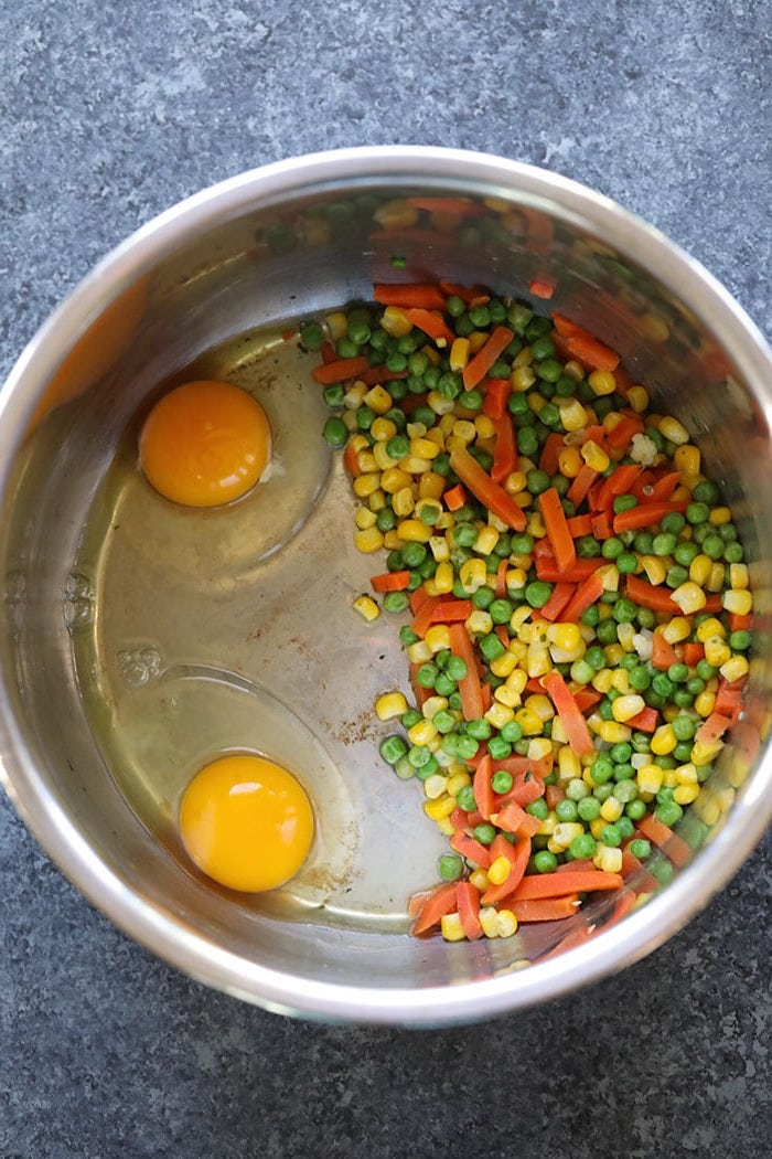corn peas carrots and two eggs placed inside instant pot bowl placed on granite gray countertop quick instant pot recipes