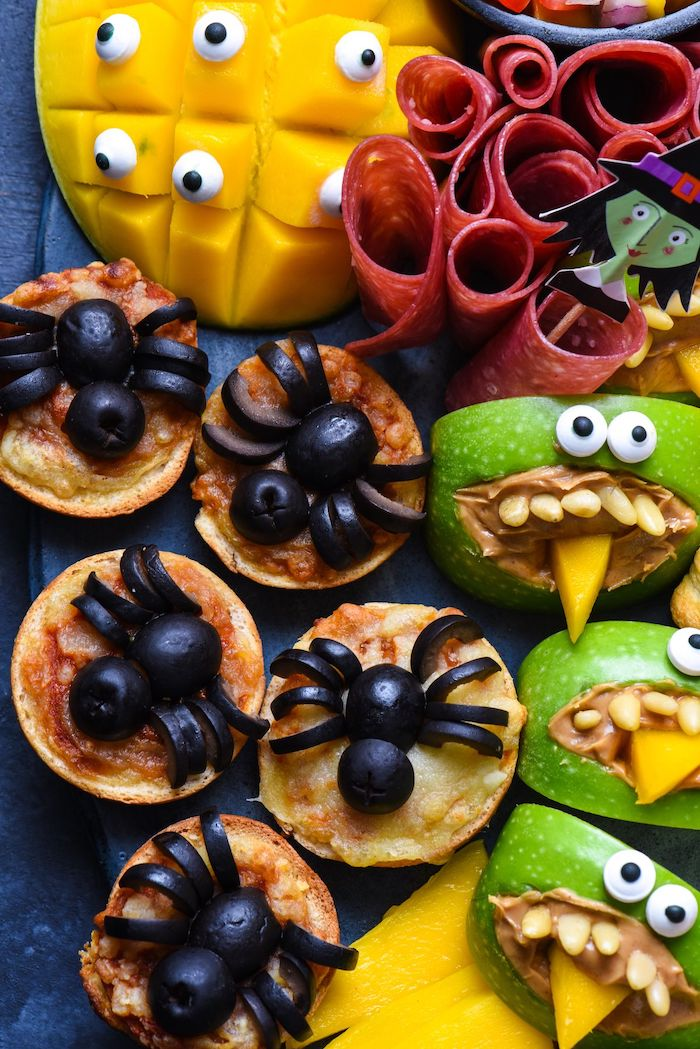 crackers with olives arranged as spiders apples with peanut butter salami mango halloween party treats arranged on black platter