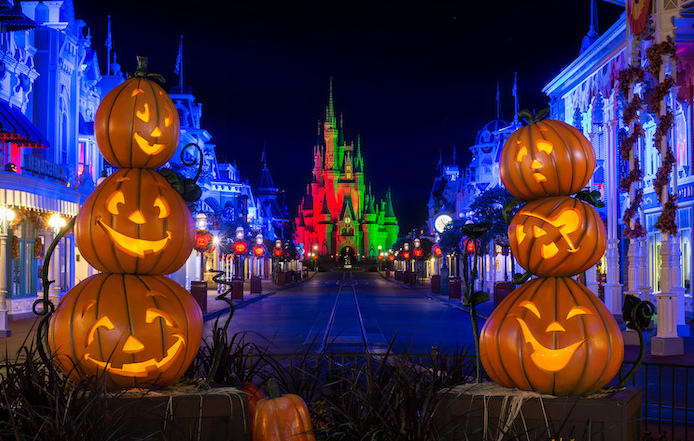 cute halloween wallpaper walt disney castle at disney world in the back long street with shops jack o lanterns decorations