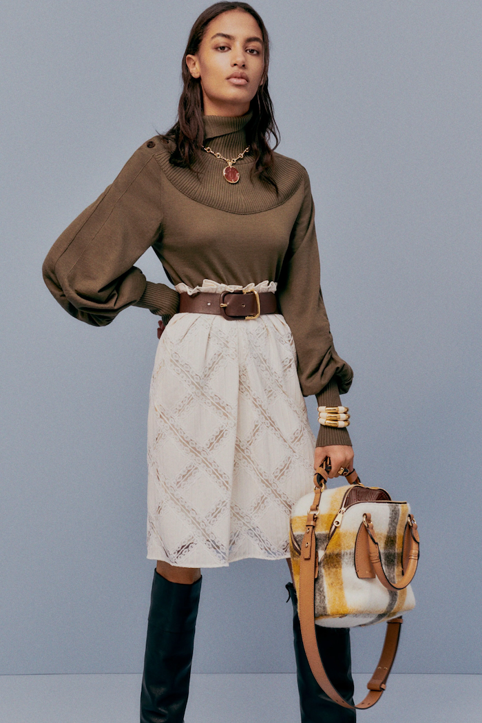 cute outfit ideas for girl brunette woman wearing brown polo blouse white skirt with brown leather belt black leather boots