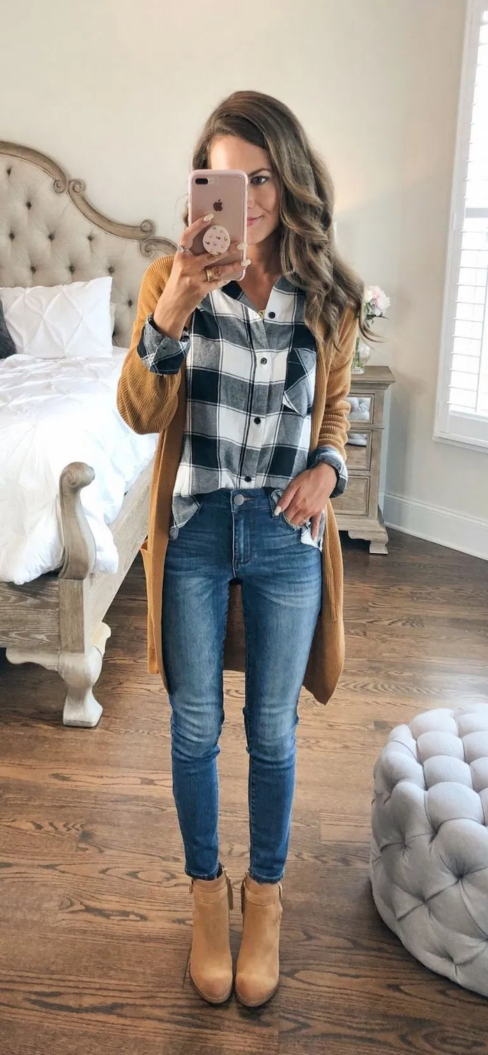 cute outfit ideas woman with light brown wavy hair taking a selfie in the mirror wearing jeans plaid shirt brown velvet boots brown cardigan