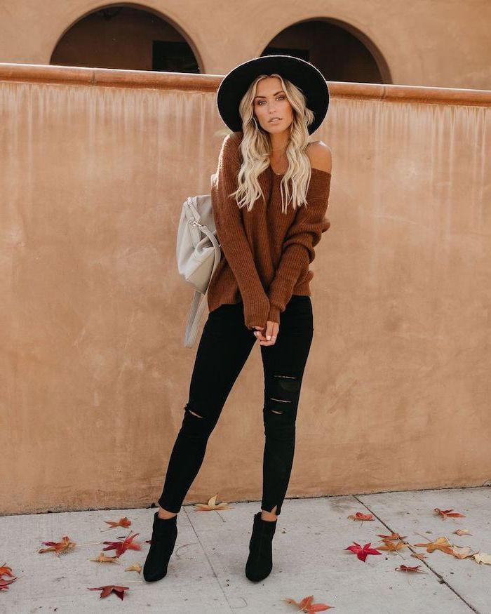 cute trendy outfits woman with long blonde wavy hair wearing black jeans brown sweater large hat brown boots
