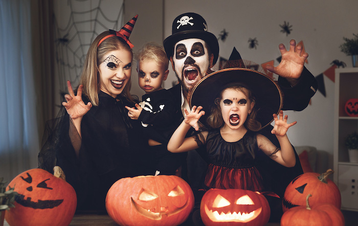 dad mom and two kids dressed in scary costumes making scary faces family of 3 halloween costumes jack o lanterns in front of them
