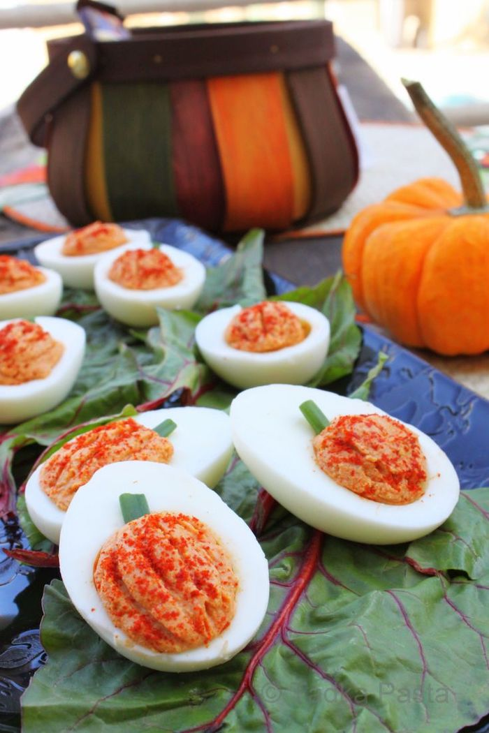 deviled eggs with filling made in the shape of pumpkin halloween party snacks arranged on green leaves on blue tray
