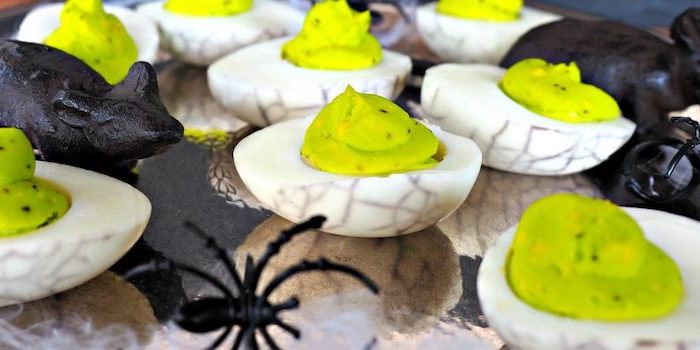 deviled eggs with green filling black dye halloween finger foods arranged on plattes with plastic spiders animals