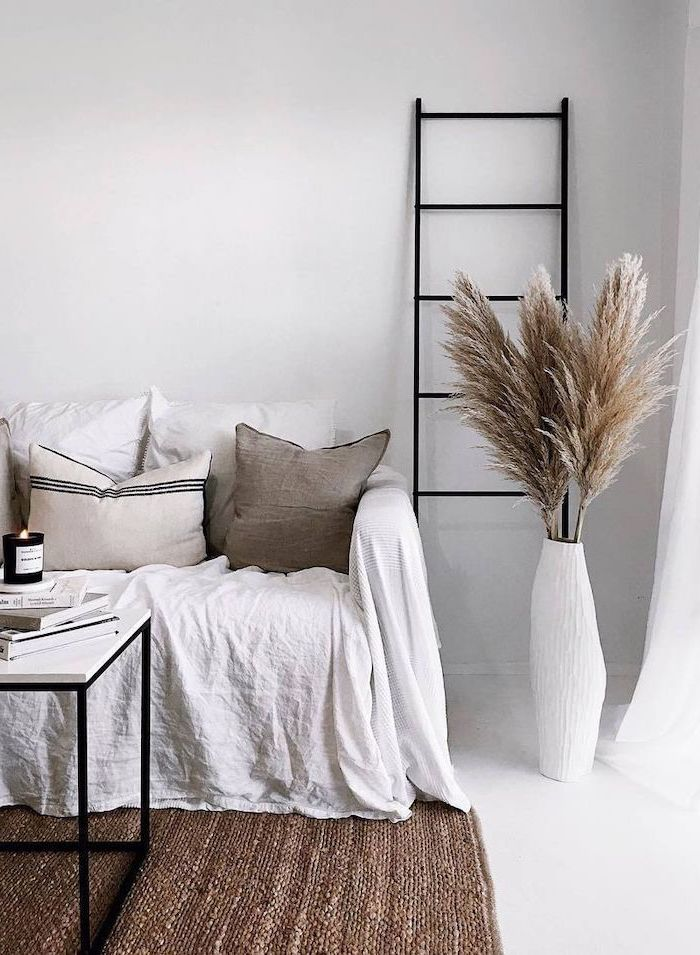 dried pampas grass inside tall white vase standing next to sofa covered with white blanket throw pillows white walls and floor