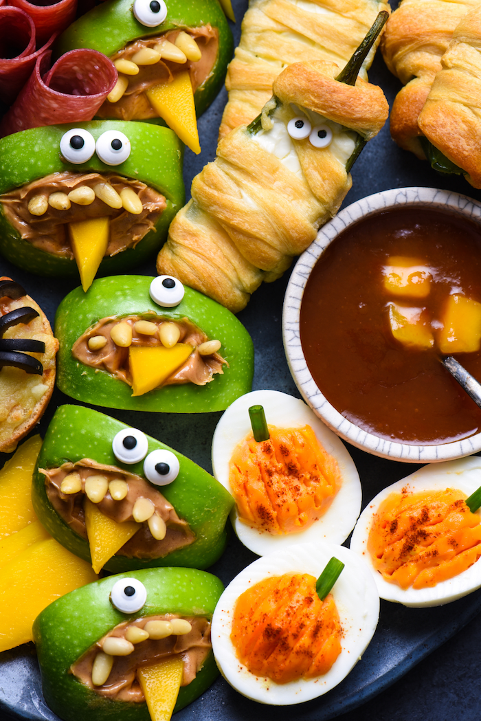 easy halloween appetizers peppers wrapped in dough as mummies salsa dip deviled eggs apples with peanut butter arranged on black paltter