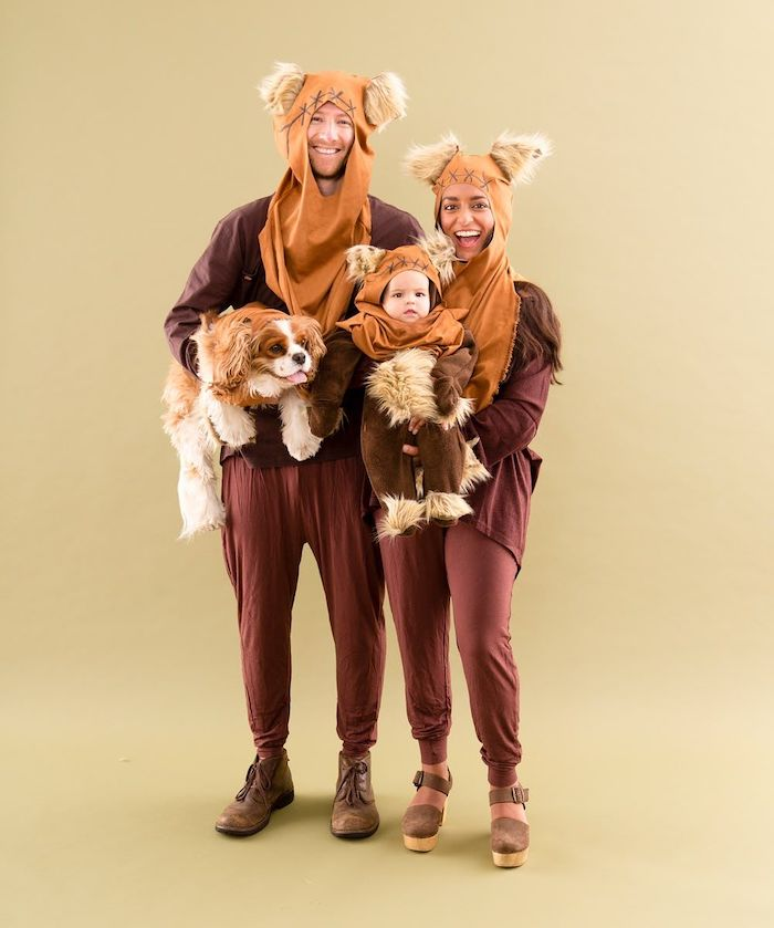 ewok costumes family of 3 halloween costumes mom holding the baby dad holding a dog photographed on yellow background