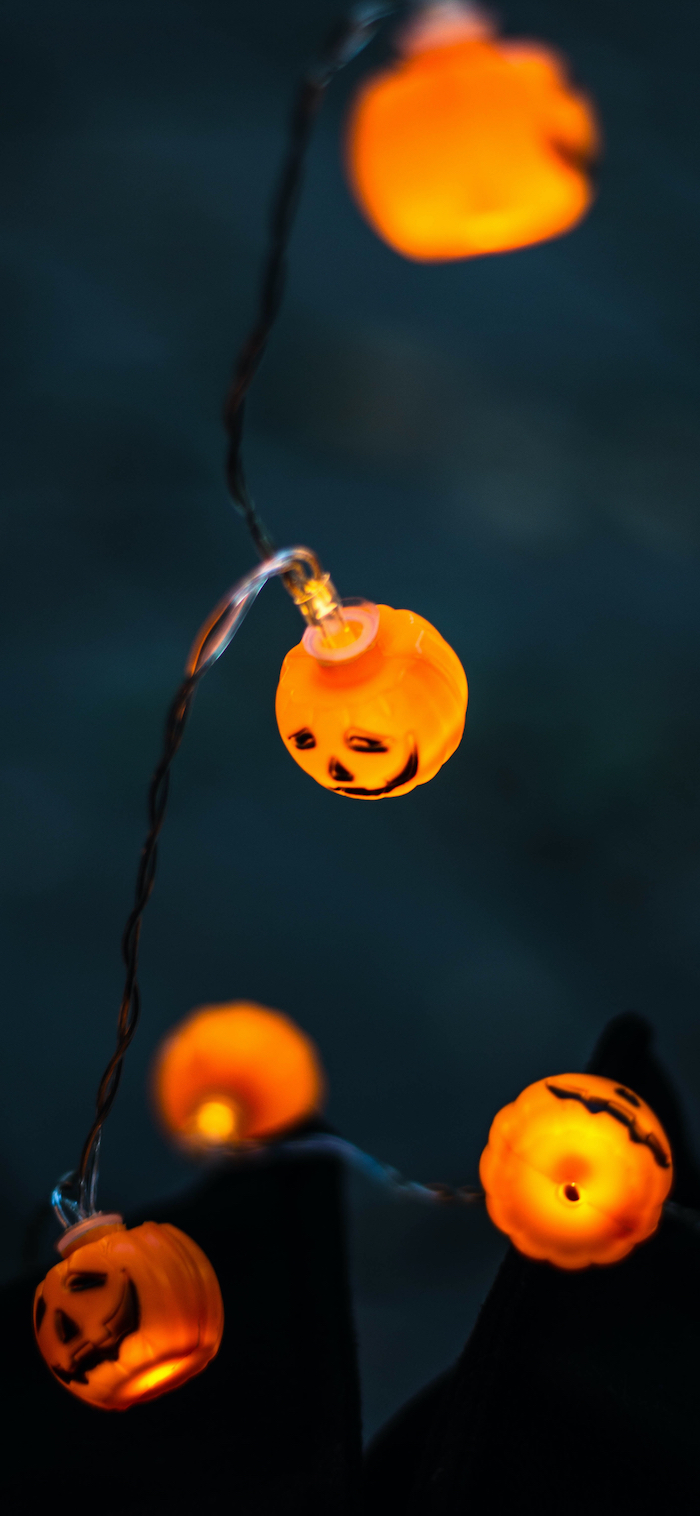 fairy lights in the shape of small jack o lanterns scary halloween wallpaper close up photo