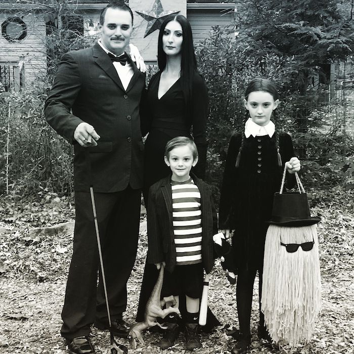 family of 3 halloween costumes family dressed as the addams family posing in old yard black and white photo