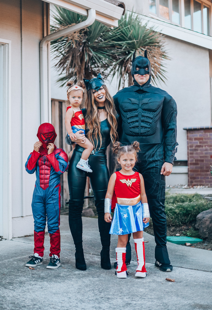 family of 4 halloween costumes mom and dad dressed as batman cat woman kids dressed as wonder woman spider man