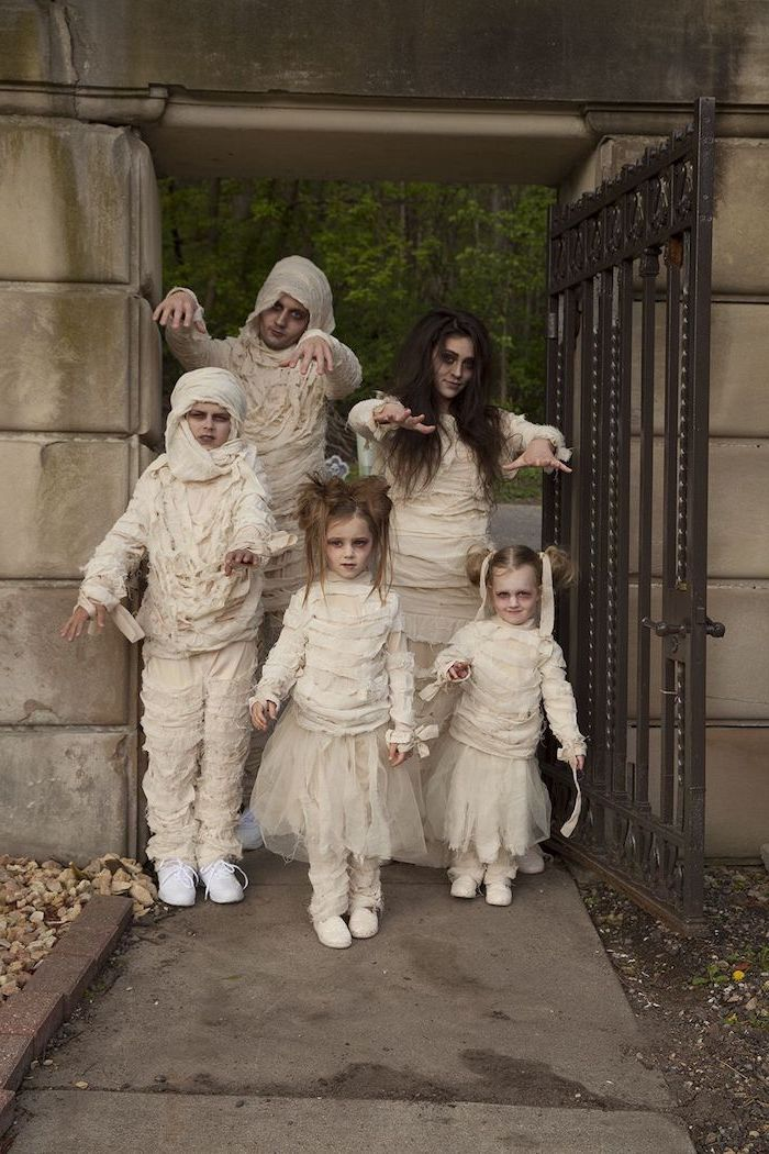 family of five dressed as mummies family halloween costumes photographed on pathway with large metal door