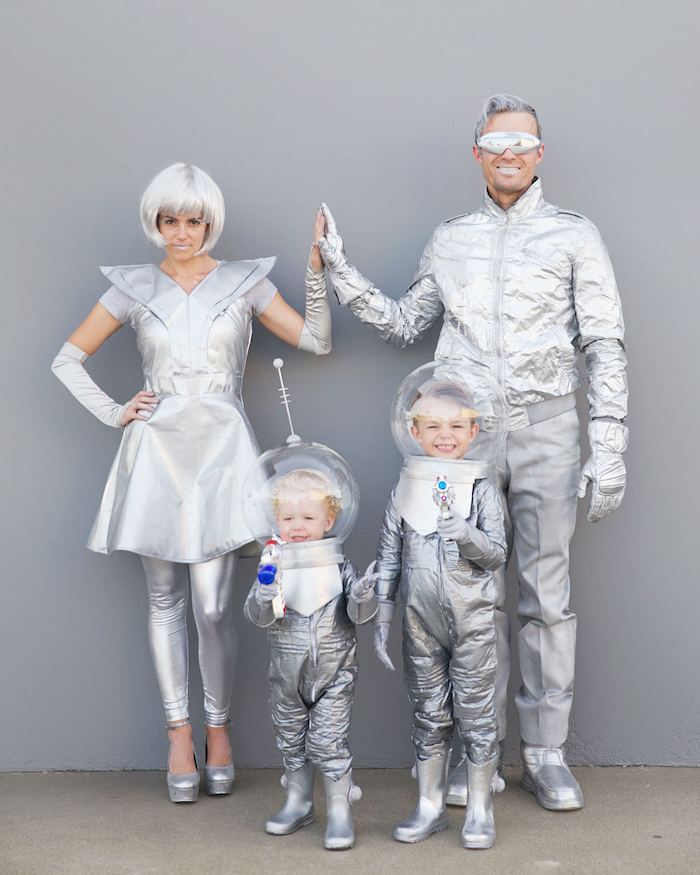 family of four dressed in all gray silver matching family halloween costumes space costumes photographed in front of gray wall