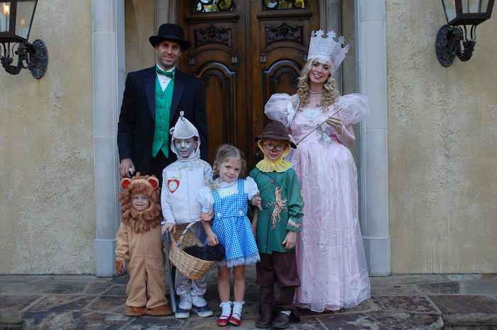 family of six dressed as characters from the wizard of oz family of 4 halloween costumes photographed in front of large wooden door