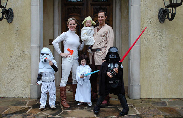 family with four kids dressed as characters from star wars family halloween costumes with baby anakin yoda princess leia darth vader stormtrooper