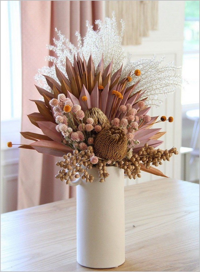 faux flowers arrangement in white pink gold dried pampas grass placed inside white ceramic vase placed on wooden table