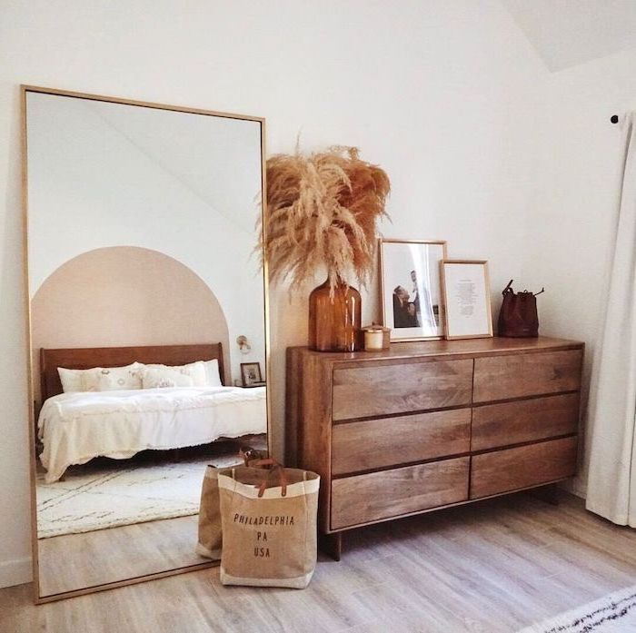 faux pampas grass wooden cupboard with framed art vase with pampas grass on top next to large mirror