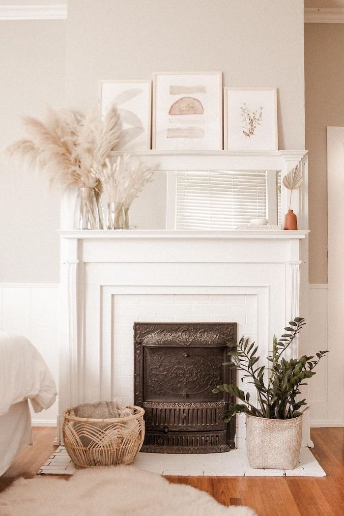 fireplace with mirror and art hanging above it pampas grass decor vases of pampas grass on the mantel